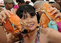 woman holding steamed crabs